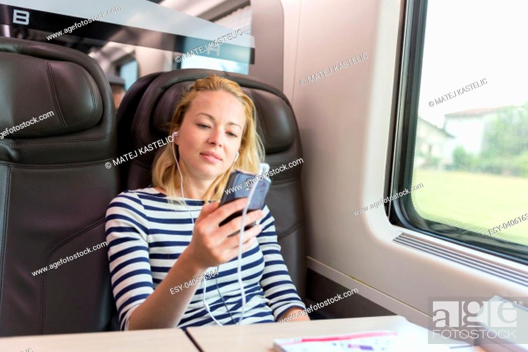 Stock Photo: Businesswoman communicating on cellphone using headphone set while traveling by train in business class seat.
