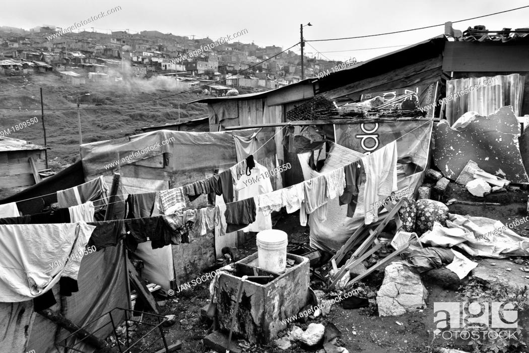 Stock Photo: Washed clothes hung out to dry in the backyard of a wooden shack, a home of the internally displaced family, slum of Ciudad Bolívar, Bogota, Colombia.