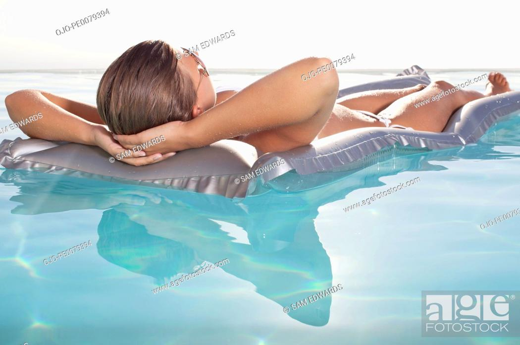 Stock Photo: Woman floating in swimming pool sunbathing.