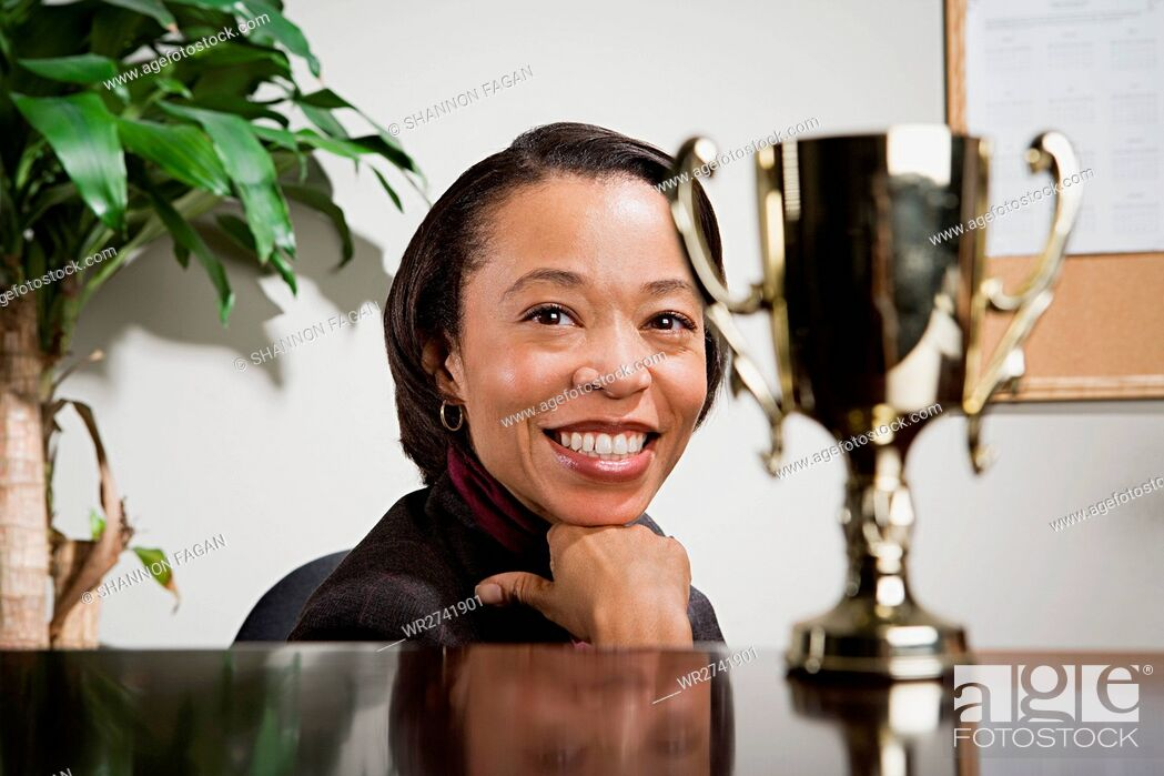 Stock Photo: Business woman admiring her trophy.
