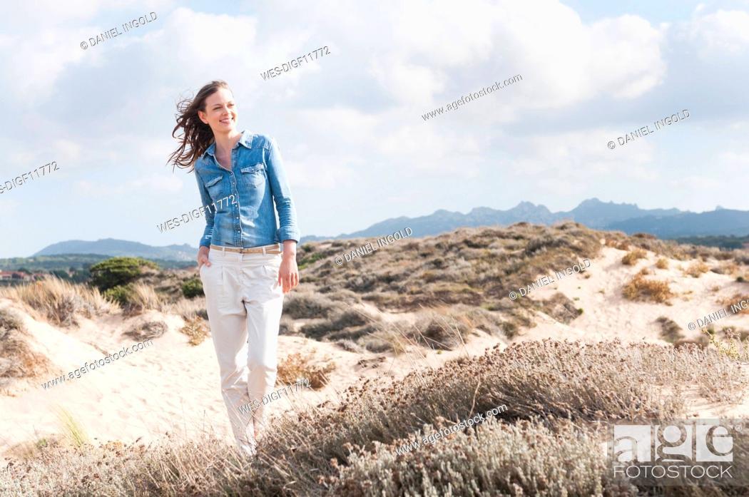 Photo de stock: Portrait of happy woman standing in beach dunes, Sardinia, Italy.