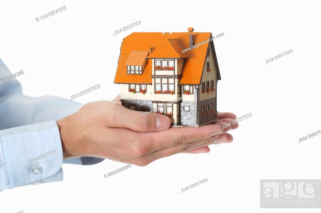 Stock Photo: Human hands holding a house model.