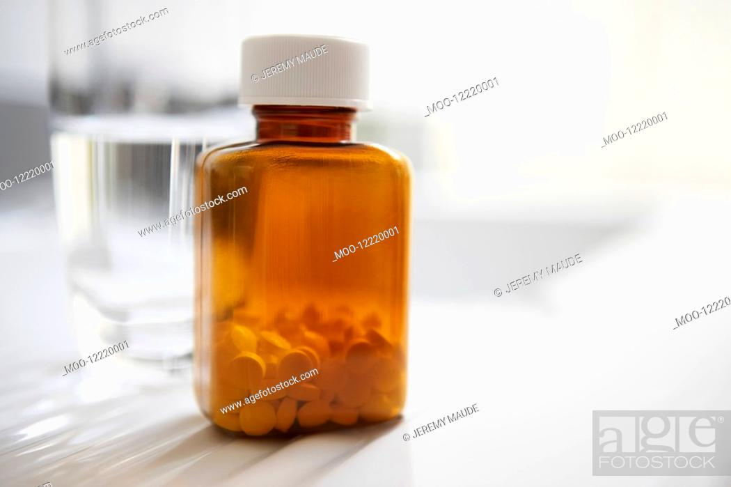 Stock Photo: Bottle of pills next to water on table close up.