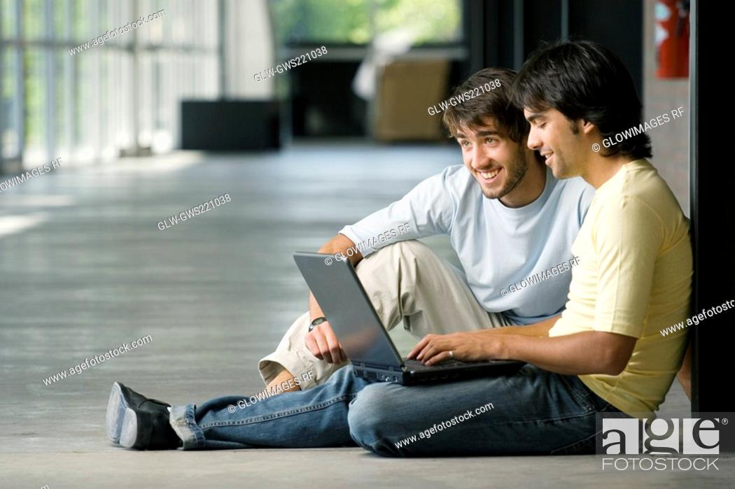 Stock Photo: Two young men working on a laptop.