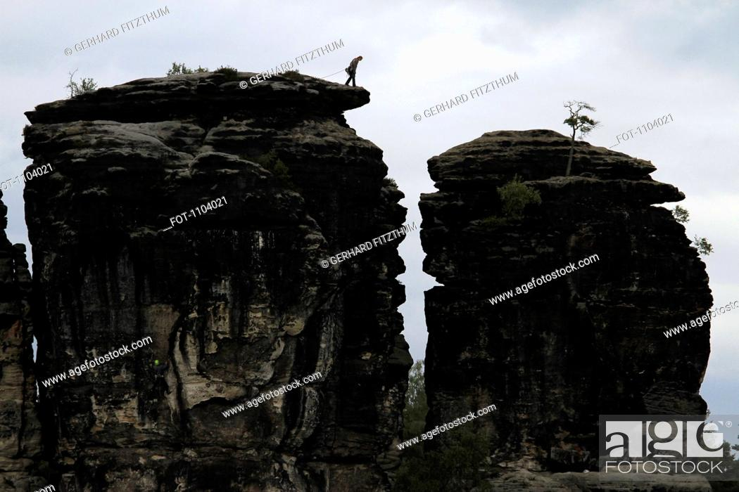 Stock Photo: A person preparing to rappel down a rock formation, Saxon Switzerland, Saxony, Germany.
