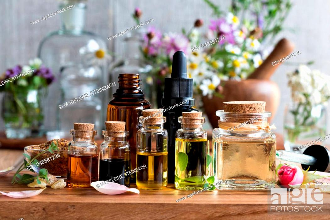Stock Photo: Selection of essential oils, with herbs and flowers in the background.
