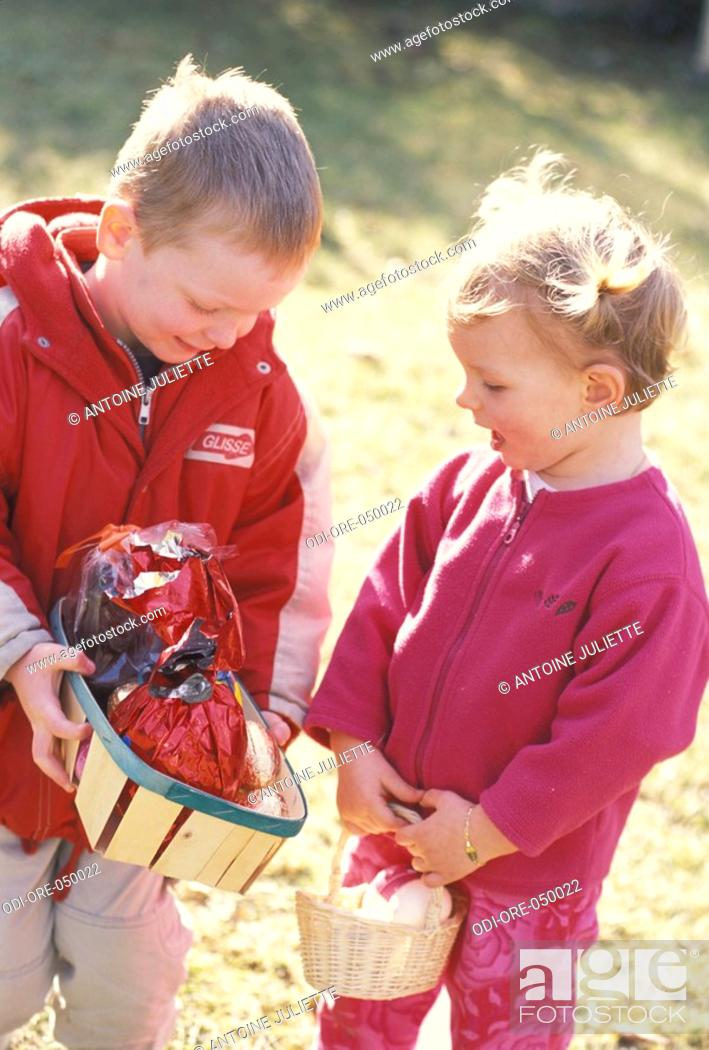 Stock Photo: children outside boy joy girl food friends sister brother complicity countryside nature garden celebration easter eggs to pick up pannier talking happiness.