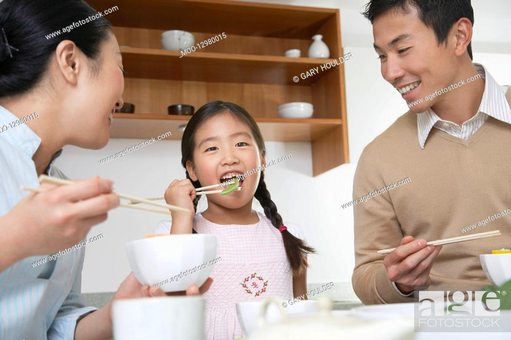 Stock Photo: Young couple and daughter eating a meal with chopsticks.