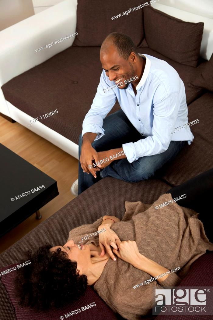 Stock Photo: A cheerful laughing couple relaxing on a sofa.