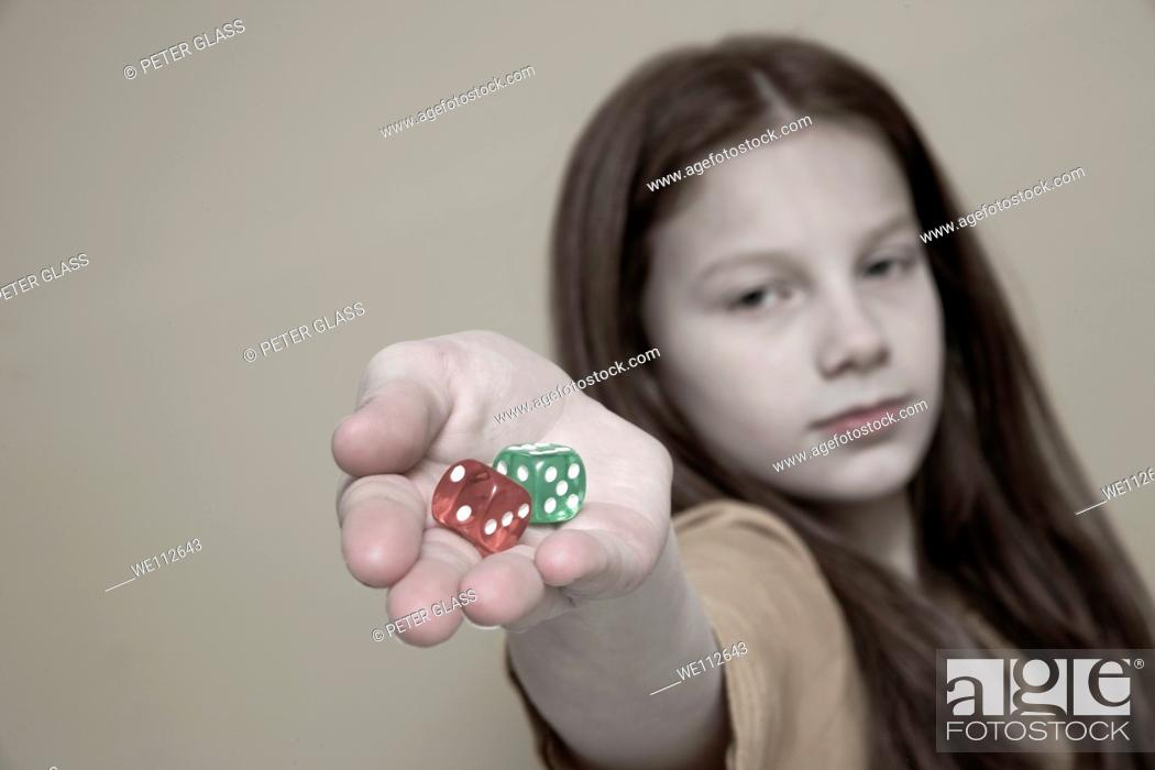 Stock Photo: Preteen girl holding colored dice.