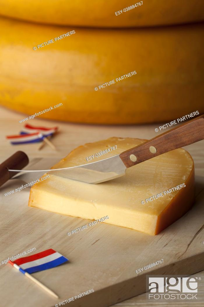 Stock Photo: Piece of Dutch mature Gouda cheese on a cutting board with flags as cocktail picks.