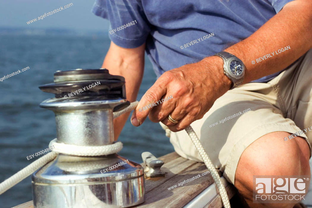 Stock Photo: Man tying a line on a winch on a sailboat.