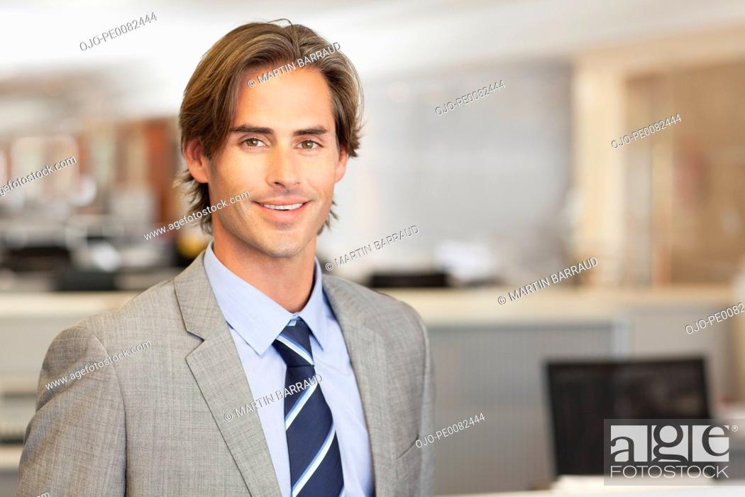 Stock Photo: Portrait of smiling businessman in office.