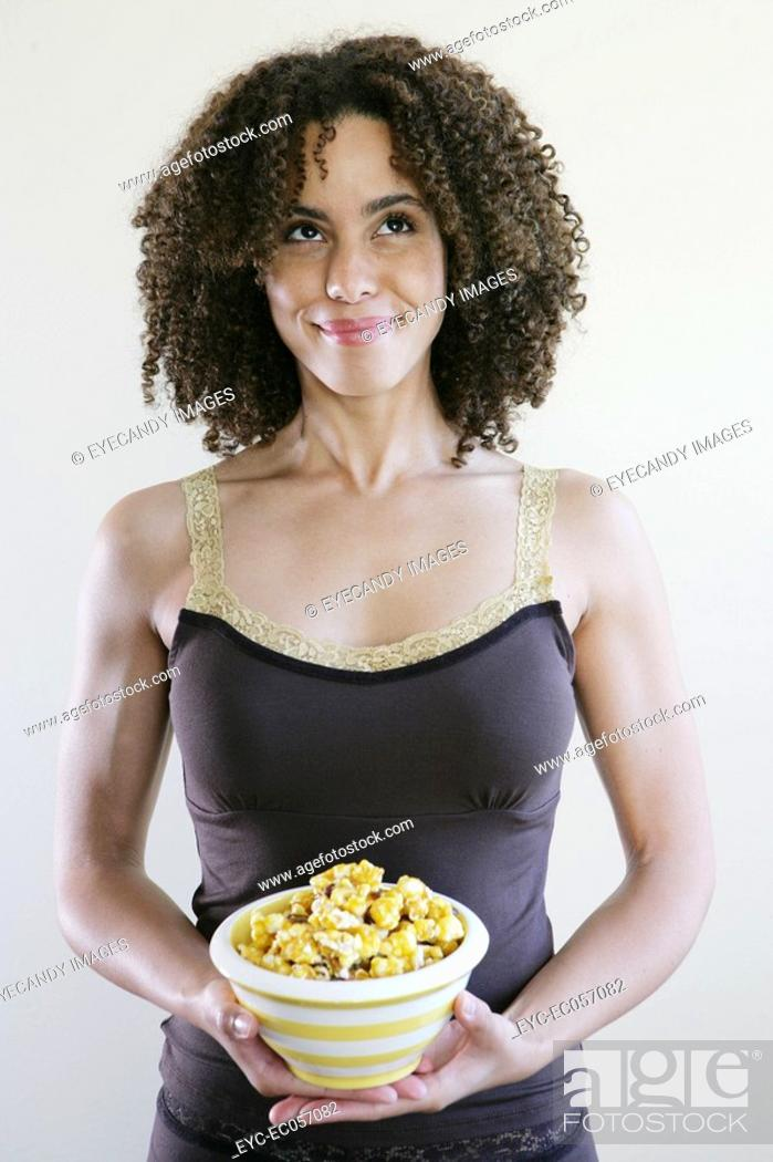 Stock Photo: Woman smiling holding a bowl of popcorn.