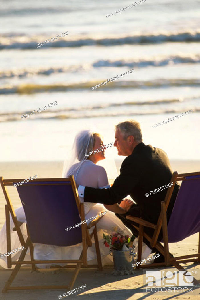 Stock Photo: Senior couple sitting on deck chairs on the beach.