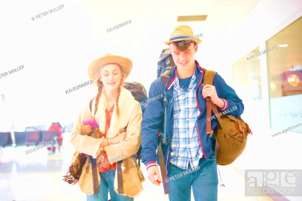 Stock Photo: Young couple at airport, carrying backpacks, setting off on journey.