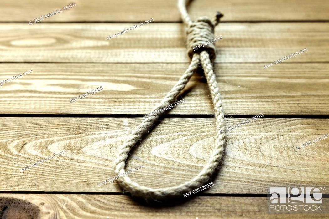 Stock Photo: sliding knot on wooden background.