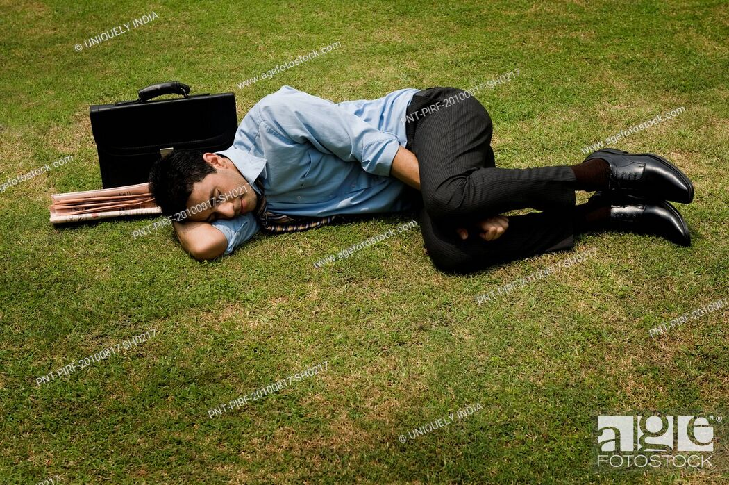 Stock Photo: Businessman sleeping in a park.