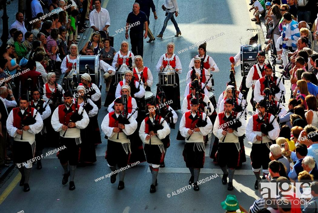 Stock Photo: Gijon pipe band marching through the streets of Llanes, Asturias Fiestas de San Roque.