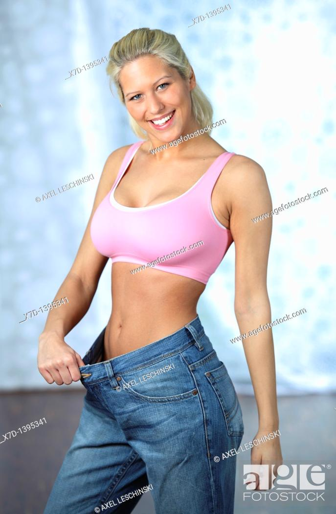 Stock Photo: blond woman showing weight loss wearing an old pair of jeans.