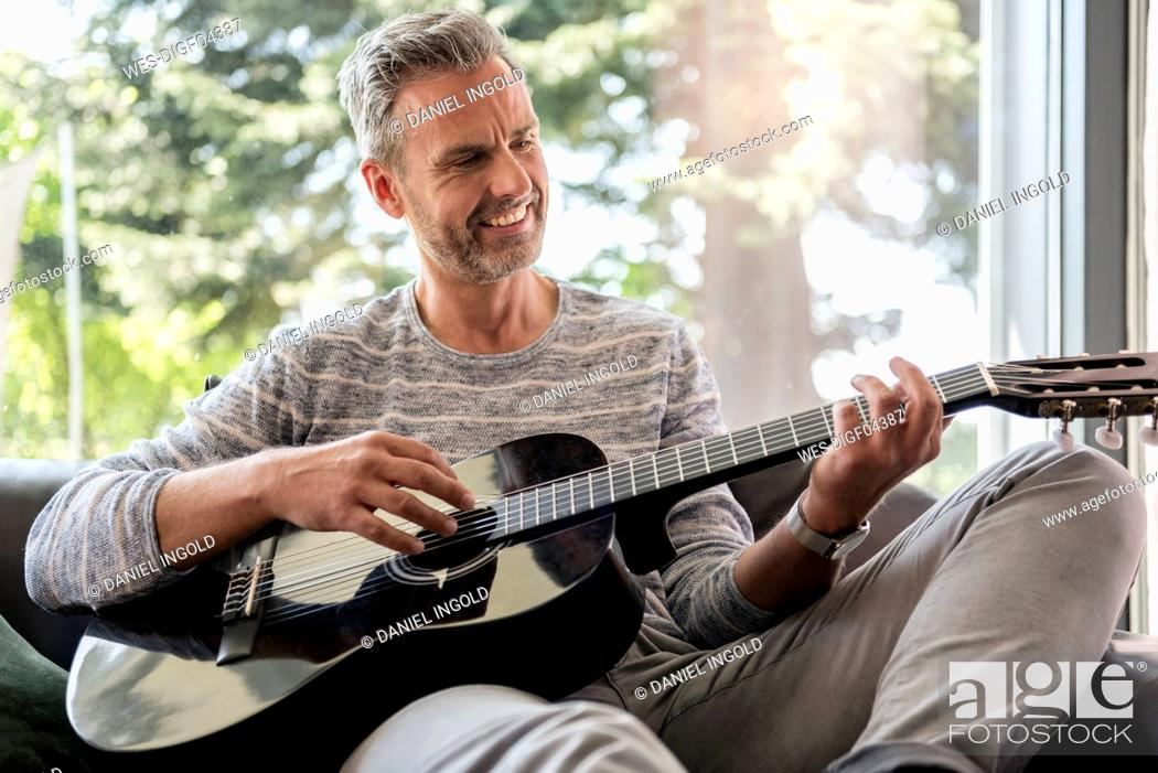 Imagen: Happy mature man lying on couch at home playing guitar.