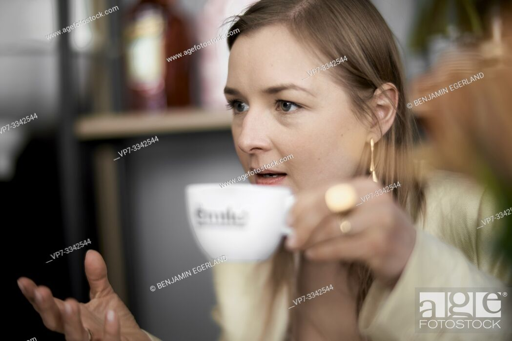 Stock Photo: concerned woman arguing with cup of tea in hands, in café.