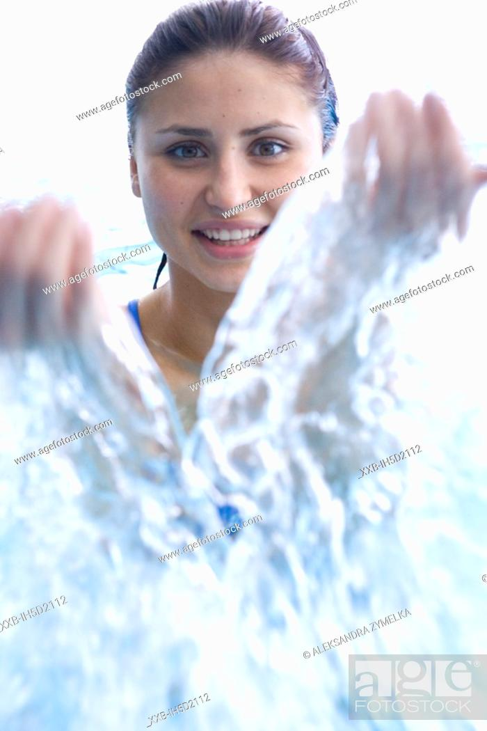 Stock Photo: young woman playing in swimming pool.