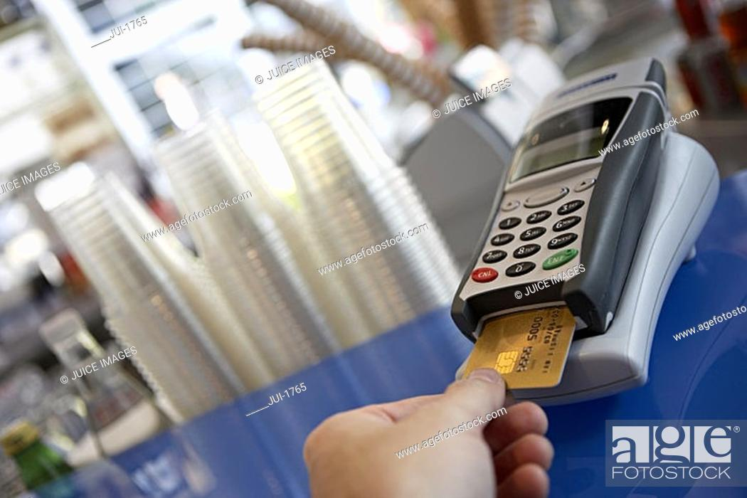 Stock Photo: Customer placing bank card in credit card reader, close-up, rear view, personal perspective tilt.