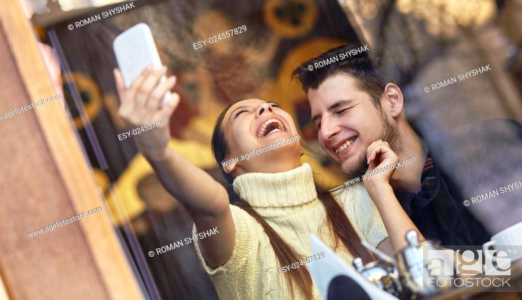 Stock Photo: Laughing young couple making selfie in the cafe.