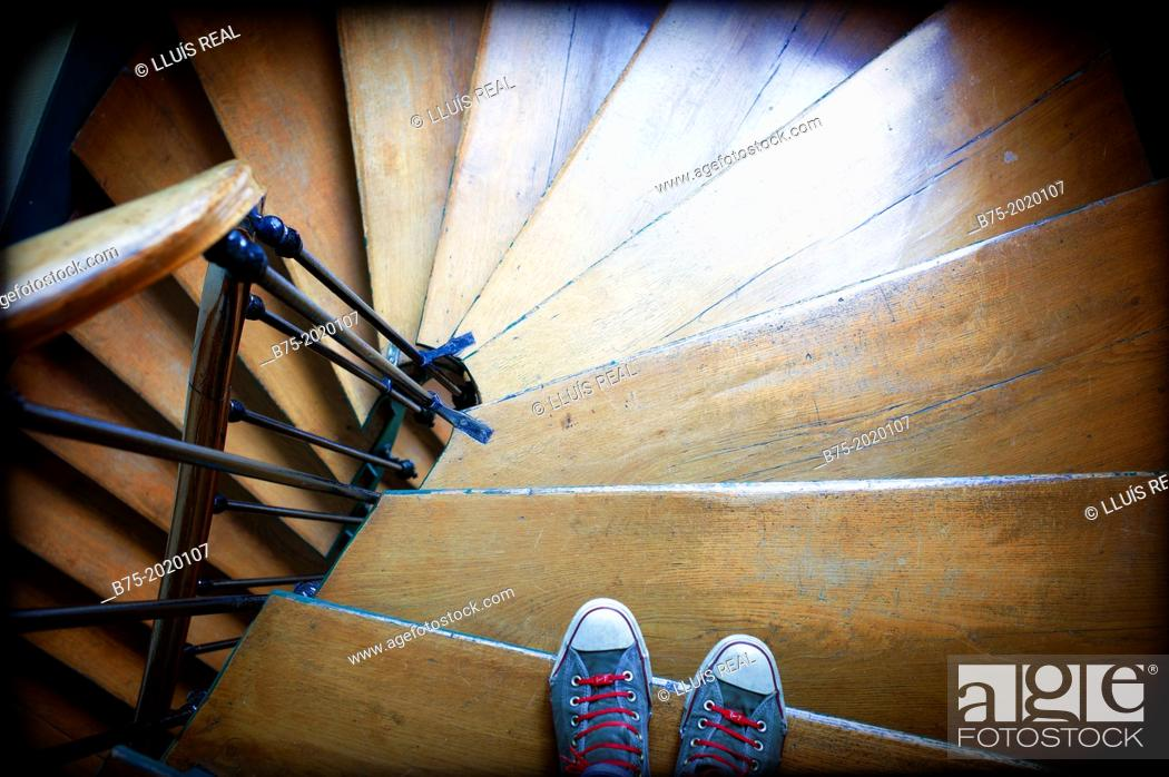 Stock Photo: Close-up of feet with sneakers going down old stairs in a building in Paris, France.