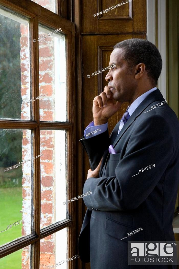 Stock Photo: Businessman looking out window, side view.