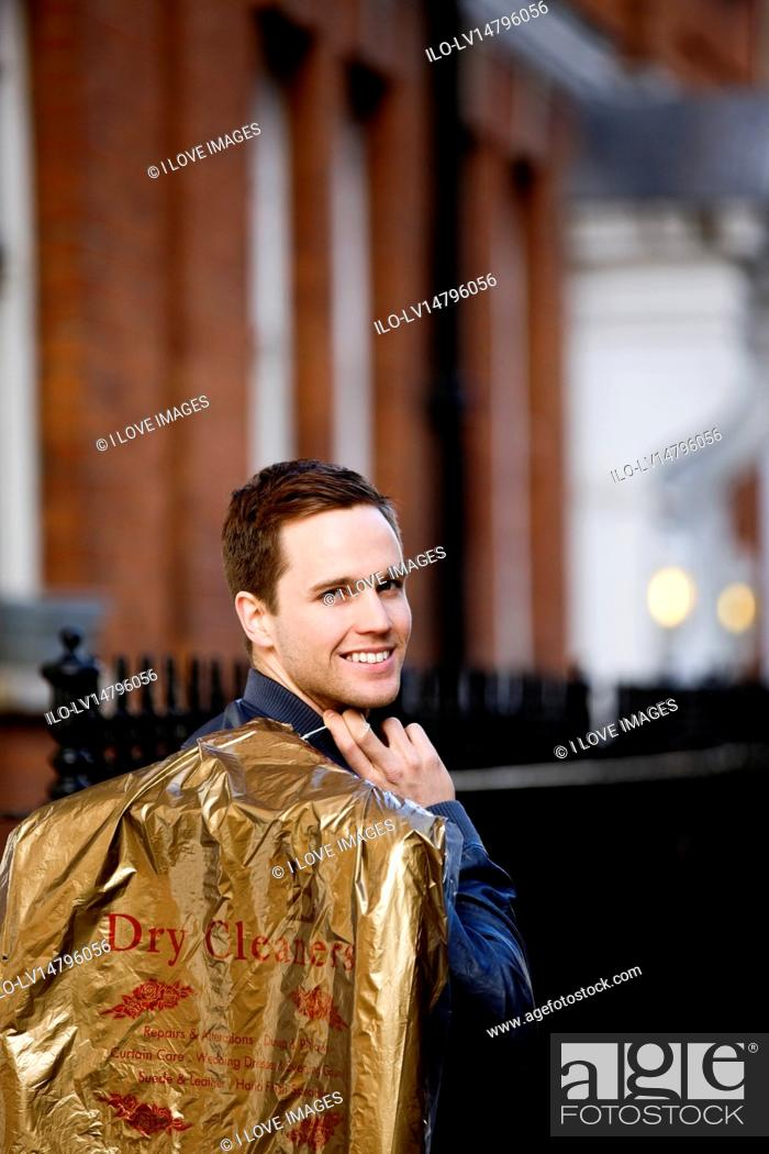Stock Photo: A young man carrying his drycleaning.