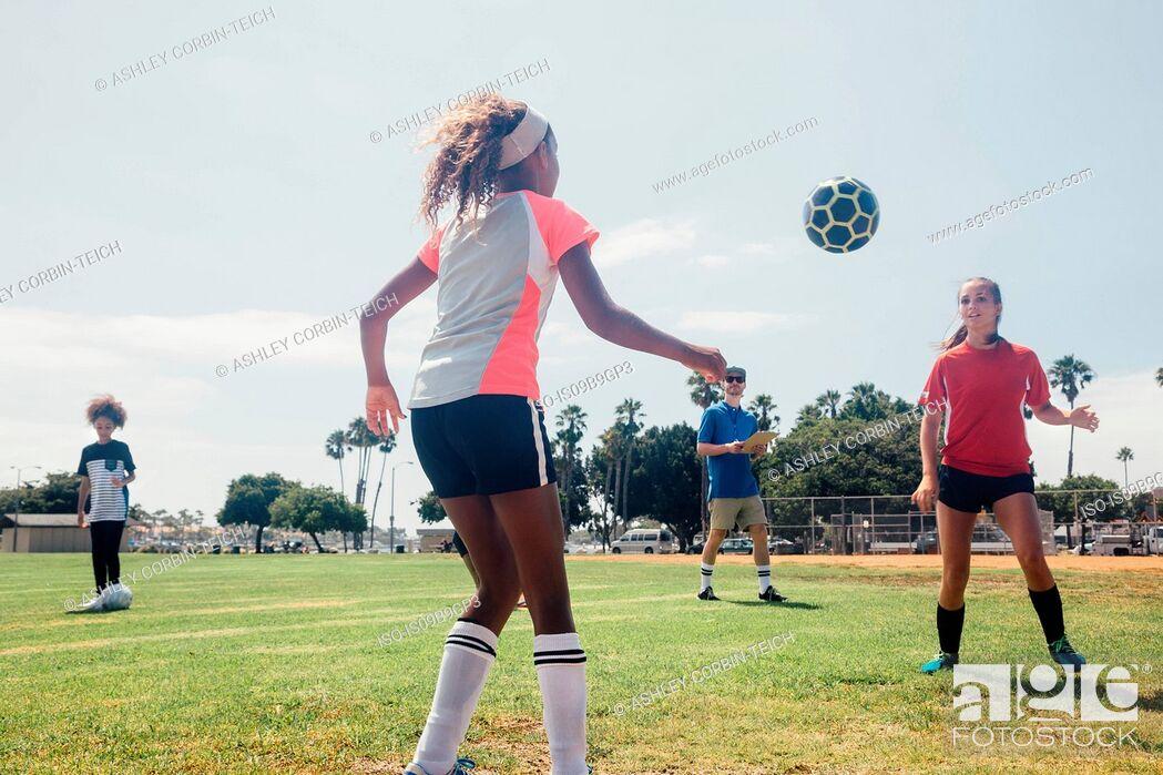 Imagen: Schoolgirls kicking ball to each other on school sports field.