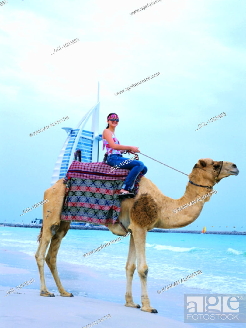 Stock Photo: Western tourist riding a camel on the beach in Dubai, United Arab Emirates.