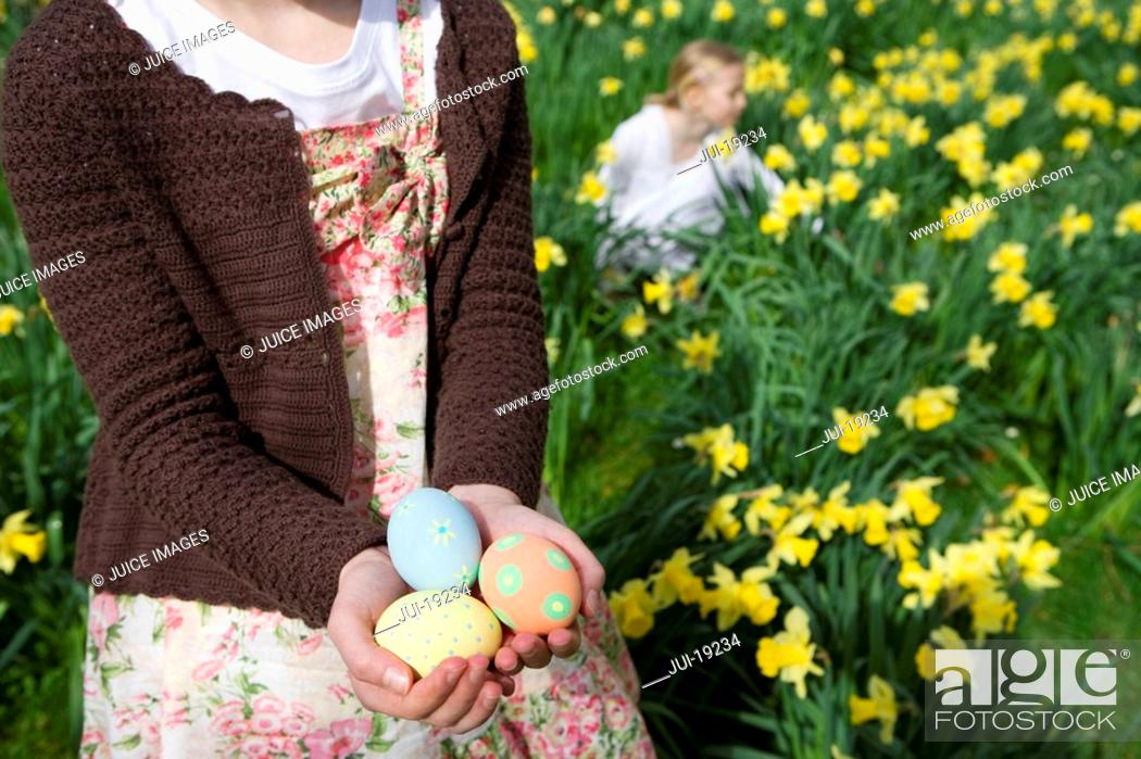 Stock Photo: Young girl holding decorated Easter eggs.