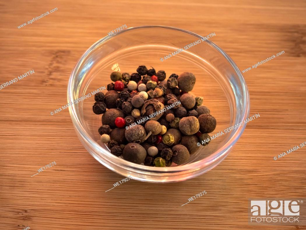 Stock Photo: Crystal bowl with white peppercorns with five peppers mix on a wooden table.