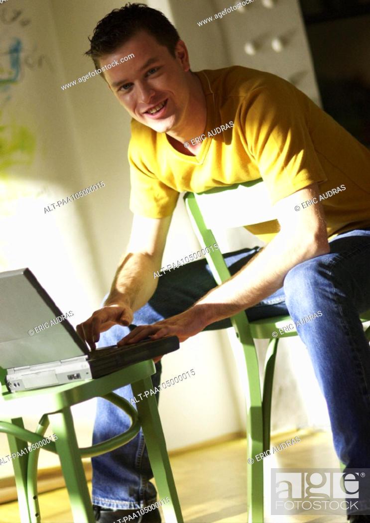 Stock Photo: Man using laptop computer, portrait.