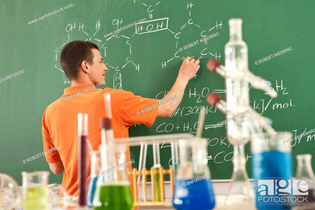 Stock Photo: Germany, Emmering, Young man writing formula on board, laboratory equipments in foreground.
