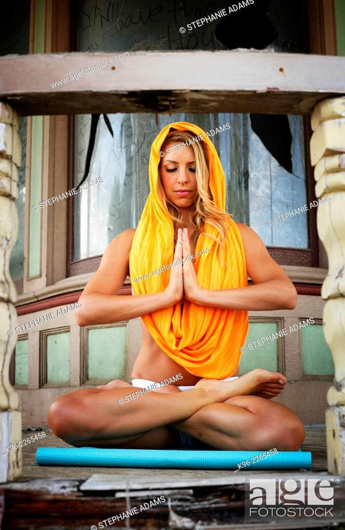 Stock Photo: Young woman practicing a meditation pose framed by old porch posts.