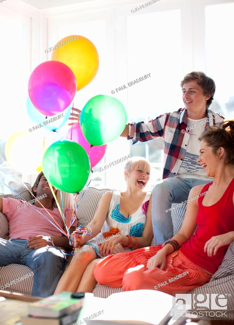 Stock Photo: Friends with balloons sitting on sofa in living room.