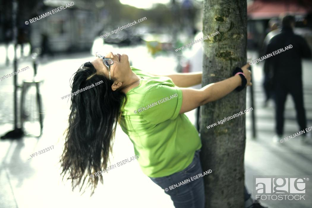 Stock Photo: eased woman embracing tree in city, in Paris, France.