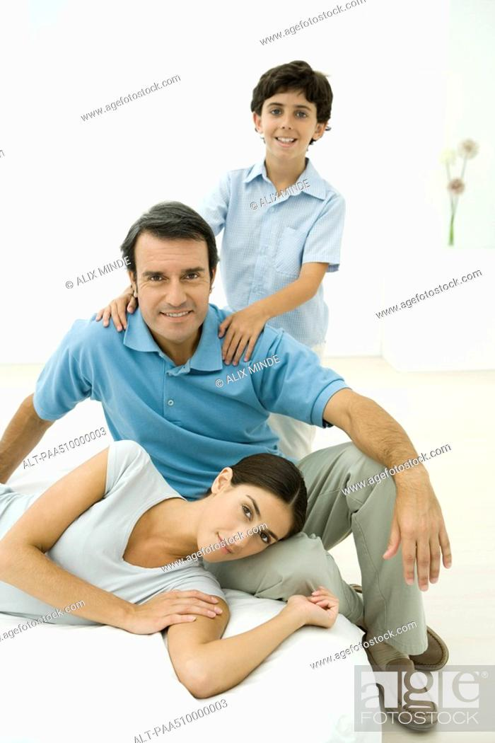 Stock Photo: Family relaxing together, all smiling at camera.