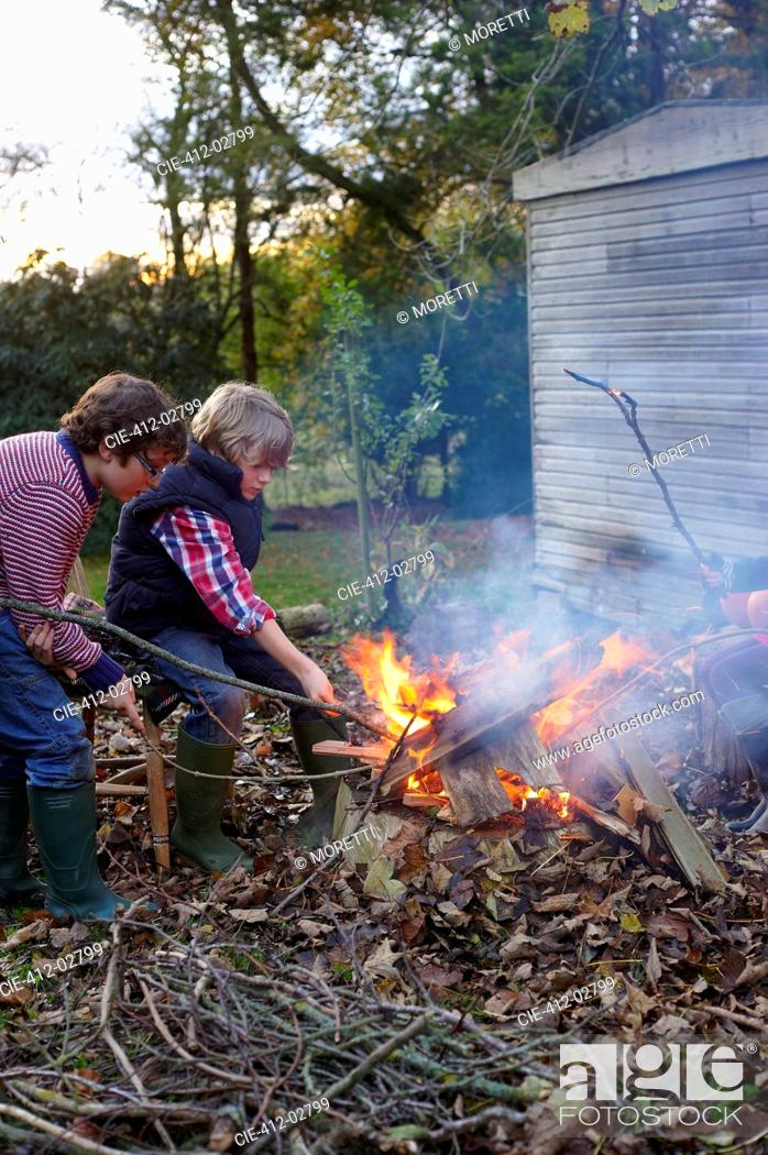 Stock Photo: Boys building bonfire outdoors.