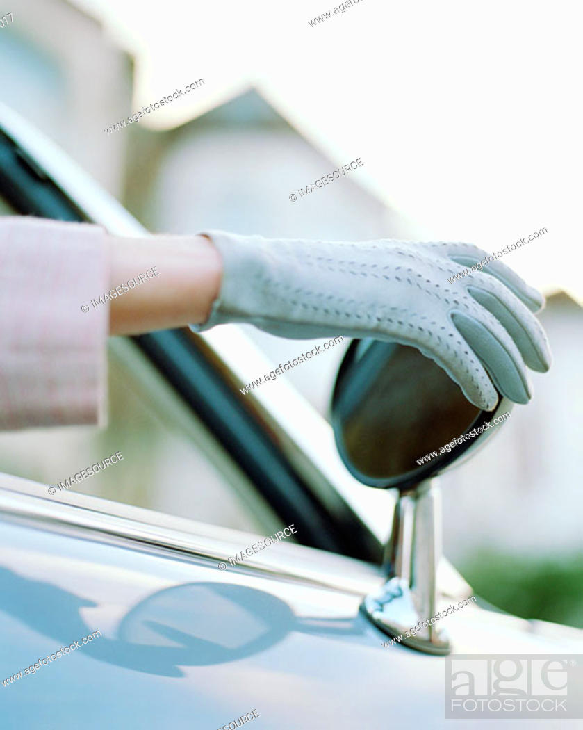 Stock Photo: Woman adjusting rearview mirror.