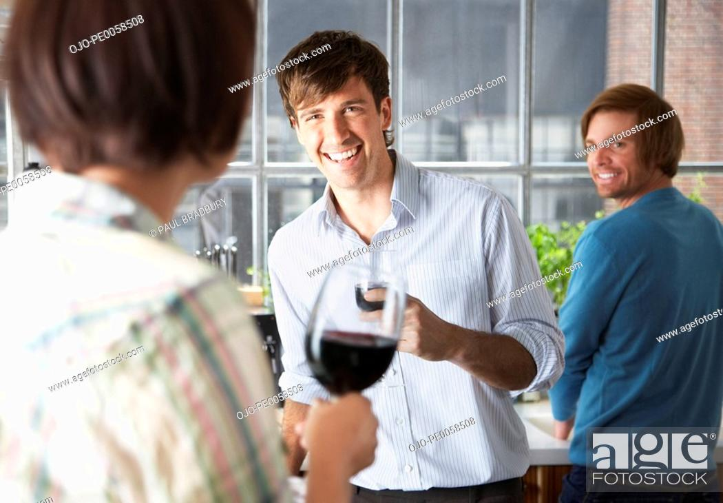 Stock Photo: Three people in kitchen with wine.