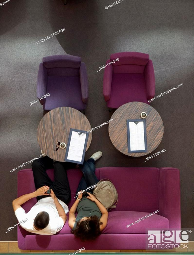Imagen: Couple using mobile phones on colorful sofa inside atrium of upmarket shopping mall on Friedrichstrasse in Berlin Germany.