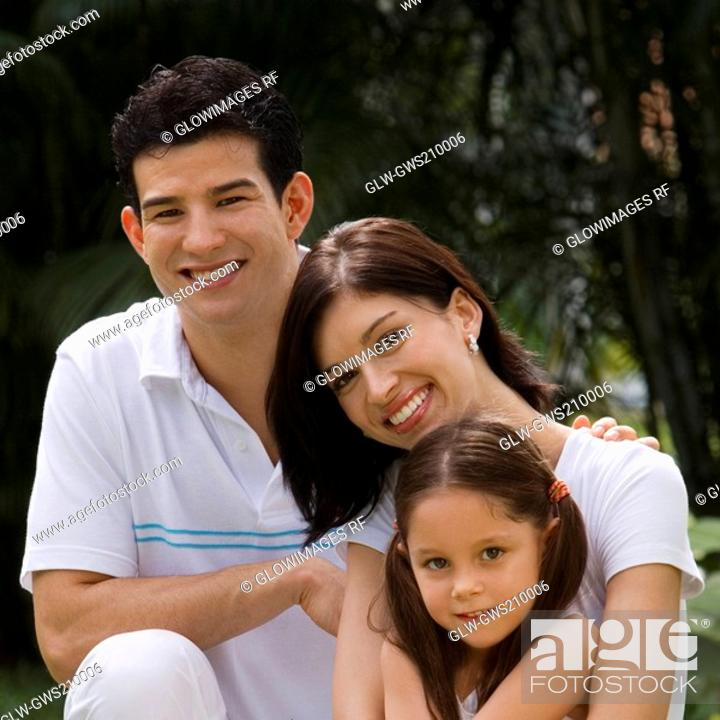 Stock Photo: Portrait of a young couple with their daughter smiling.