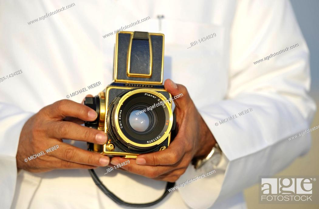 Arabians presenting his gilded Hasselblad with Carl Zeiss Planar