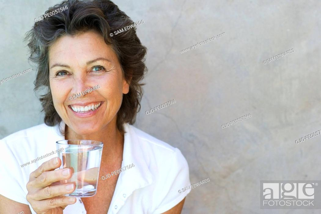 Stock Photo: Woman smiling holding a glass of water outdoors.