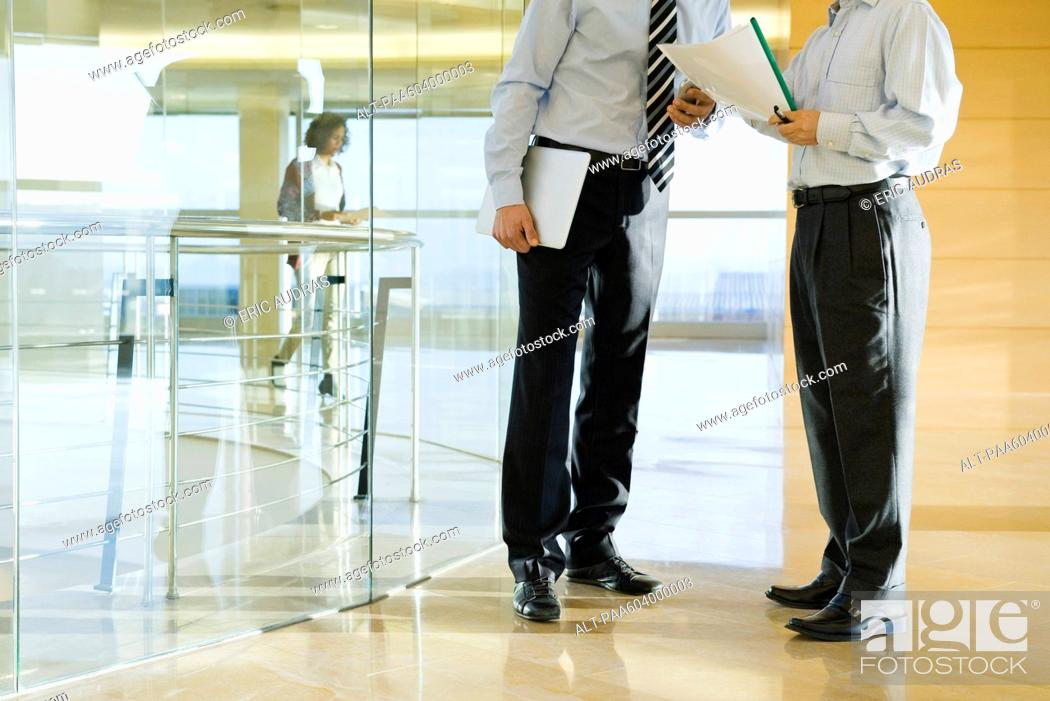 Stock Photo: Businessmen discussing document in corridor, cropped.